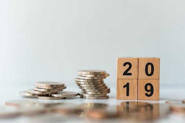 Holzblock 2019 mit stapel von münzen unter verwendung als geschäfts- und finanzkonzept Premium Fotos