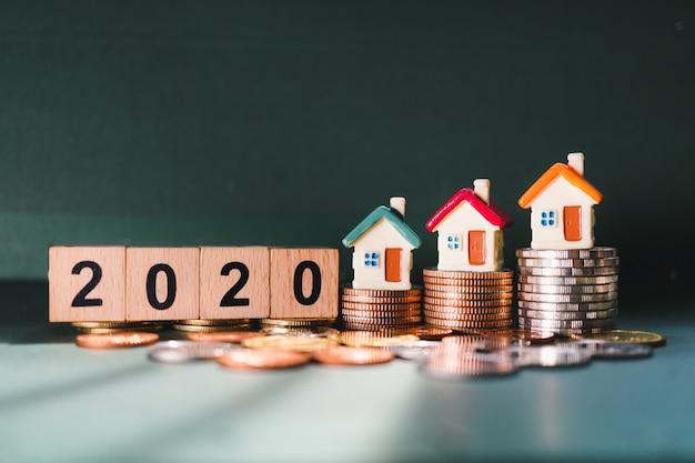 Holzblockjahr 2020 und mini-haus auf stapelmünzen unter verwendung als geschäftsfinanz- und immobilienimmobilienkonzept Premium Fotos
