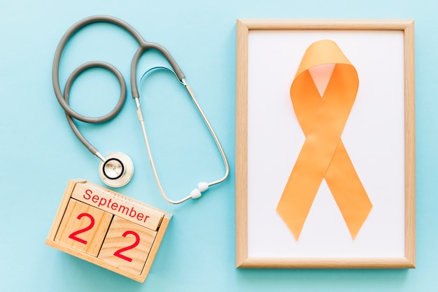 Holzblockkalender am 22. september, stethoskop und orange band für mehr bewusstsein Kostenlose Fotos