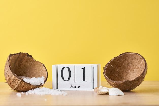 Holzblockkalender mit datum 1. juni und kokosnuss mit meersalz auf gelbem hintergrund. sommerferienkonzept Premium Fotos
