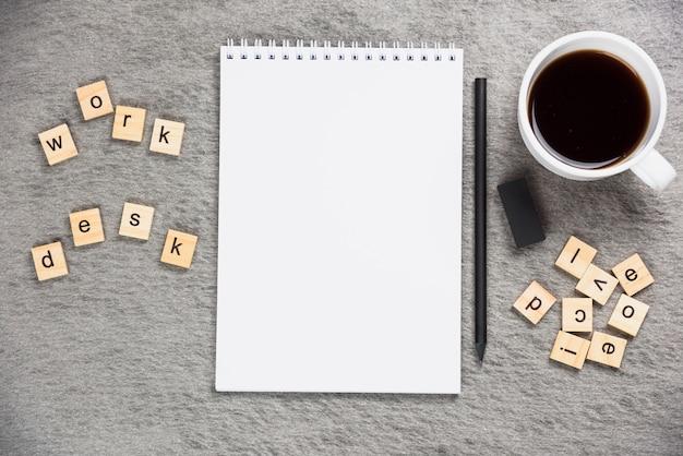 Holzblöcke am schreibtisch mit leerem notizblock; bleistift; gummi und kaffeetasse auf grauem hintergrund Kostenlose Fotos