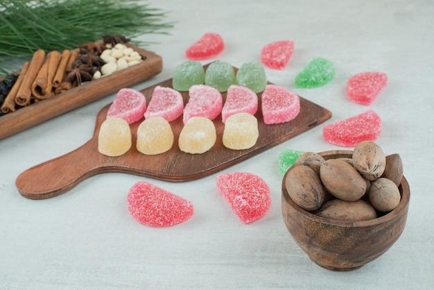 Holzbrett voller zuckermarmelade auf weißem hintergrund. hochwertiges foto Kostenlose Fotos