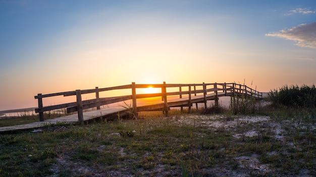 Holzbrücke in einem feld mit einem see während des sonnenuntergangs in portugal Kostenlose Fotos