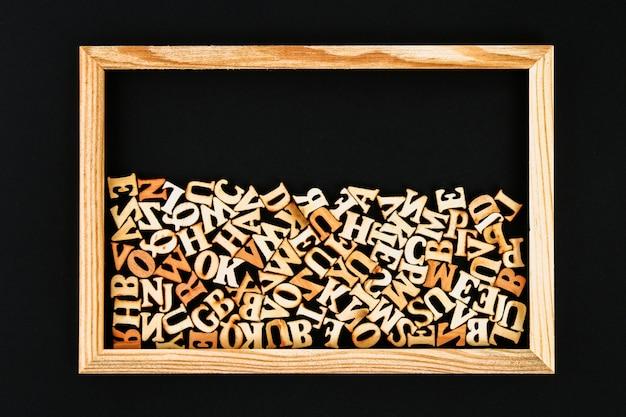 Holzbuchstaben in einem holzrahmen auf einer tafel. das konzept des lesens, wissens, studiums. Premium Fotos