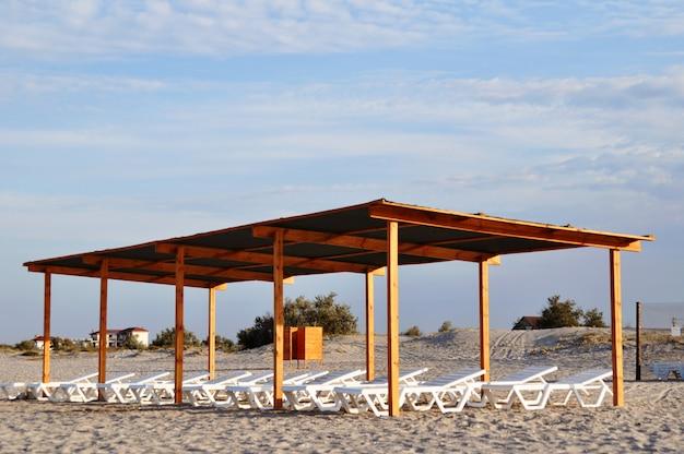 Holzdach mit liegestühlen am strand im morgengrauen. Premium Fotos