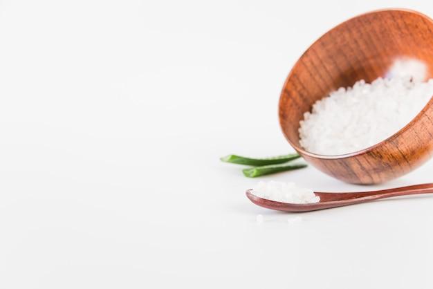Hölzerne Schüssel und Löffel mit Steinsalz auf weißem Hintergrund Kostenlose Fotos