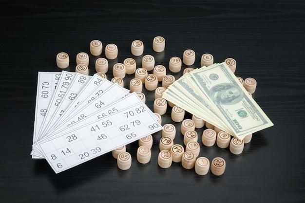 Holzfässer lotto, karten und dollar. schwarzer holztisch. Premium Fotos