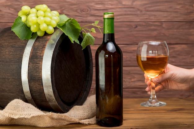 Holzfass mit flasche und glas wein Kostenlose Fotos