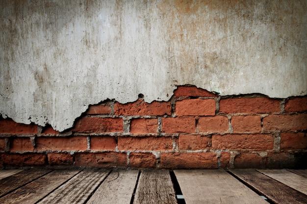 Holzfußboden im alten raum mit backsteinmauer, grungy hintergrund Premium Fotos