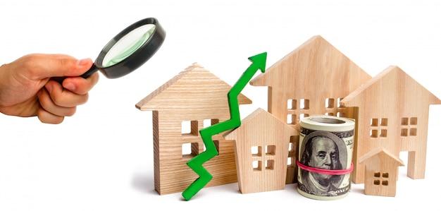 Holzhäuser mit einem grünen pfeil nach oben. konzept der hohen nachfrage nach immobilien. Premium Fotos