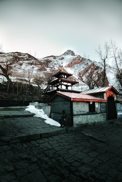 Holzhaus gegen schneebedeckte hügel im winter Kostenlose Fotos