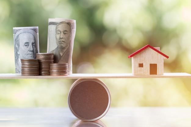 Holzhaus, münzengeld, us-dollar, jpy auf hölzerner runder kastenbalance für das träumen von häusern Premium Fotos