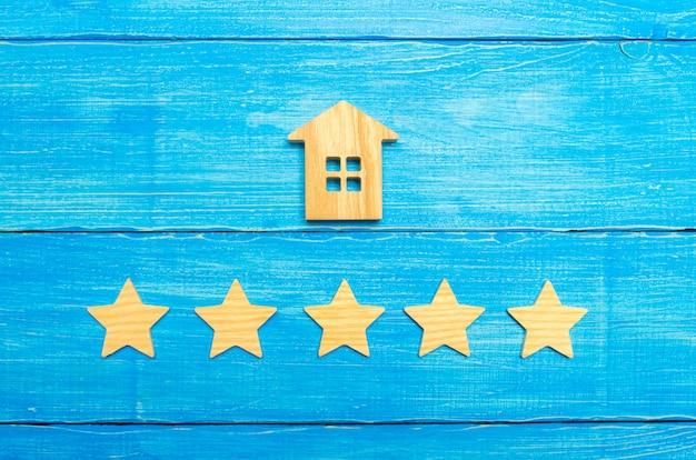 Holzhaus und fünf sterne auf grauem hintergrund. bewertung von häusern und privateigentum. Premium Fotos