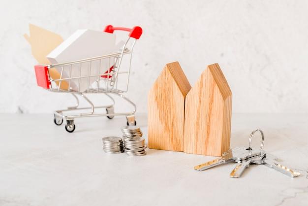 Holzhausblöcke; stapel von münzen; schlüssel und kleiner einkaufswagen auf konkreten hintergrund Kostenlose Fotos