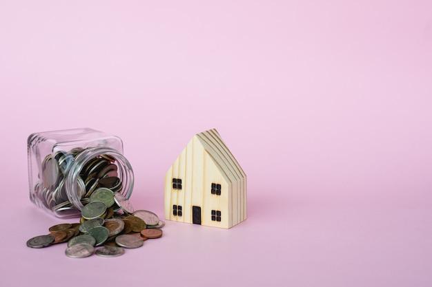 Holzhausmodell mit geldmünzen im glas auf rosa hintergrund mit kopienraum für geschäft und finanzen für immobilienkonzept Premium Fotos