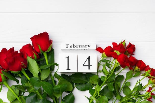 Holzkalender 14. februar und rosen auf weißem hintergrund flach liegen Premium Fotos
