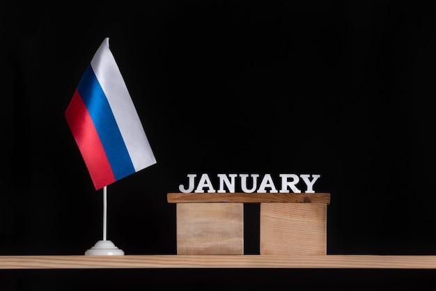 Holzkalender von januar mit russischer flagge auf schwarzraum. termine in russland im januar. Premium Fotos