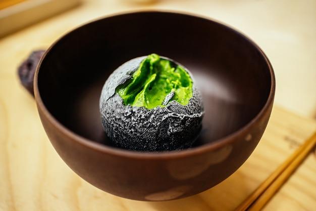 Holzkohle beschichtete eine kugel hausgemachtes grüntee-eis im japanischen teehaus-dessertcafé. leckeres exotisches fusion-dessert im asiatischen stil. Premium Fotos