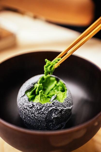 Holzkohle überzog eine kugel grüntee-eis, die mit stäbchen gekniffen wurde. Premium Fotos