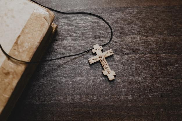 Holzkreuz und altes bibelbuch auf holztisch Premium Fotos