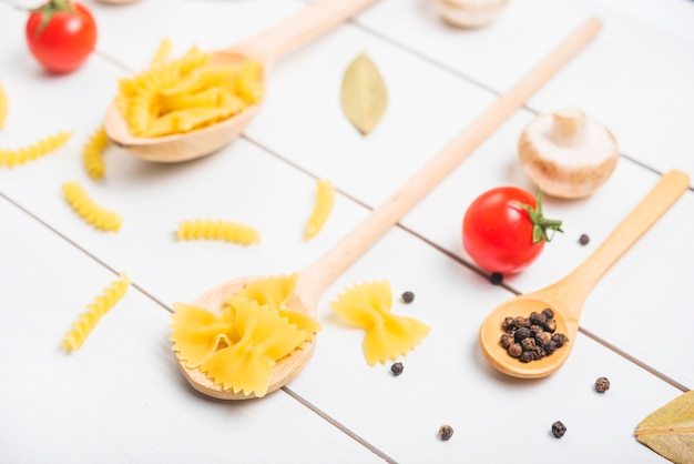 Holzlöffel mit nudeln fusilli; farfalle und pfefferkörner mit tomaten; pilz; lorbeerblatt Kostenlose Fotos