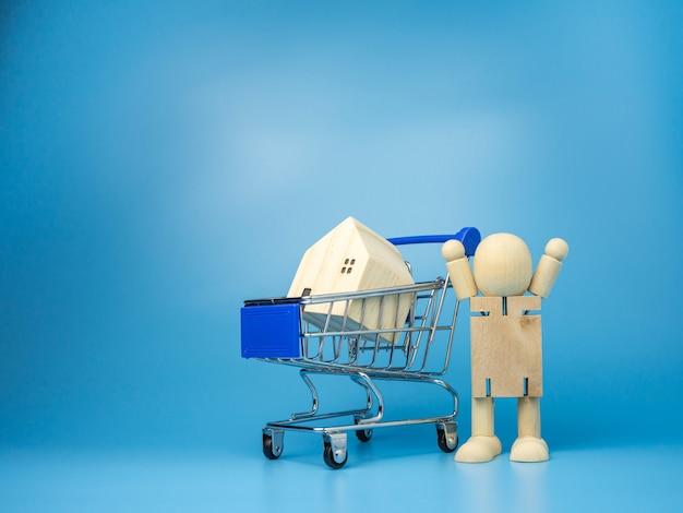 Holzpuppen, die neben dem einkaufswagen stehen mit einem modellholzhaus auf blau Premium Fotos