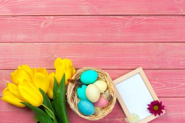 Holzrahmen mit ostereiern und tulpen auf buntem hintergrund Premium Fotos