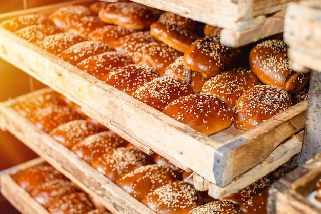 Holzregale mit frischem gebäck in einer bäckerei. sesambrötchen. Premium Fotos