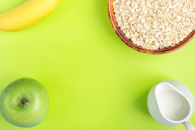 Holzschale mit gerollten oates, weißem krug, milch, bananengrünem apfel auf pistazienhintergrund. Premium Fotos