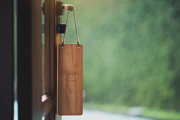 Holzschild mit dem text lächeln, das vor dem raum hängt Premium Fotos