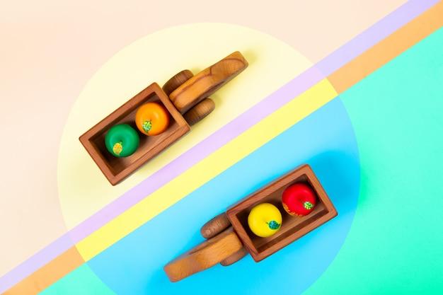 Holzspielzeug lkw mit äpfeln auf einem isolierten bunten lebendigen geometrischen hintergrund. Premium Fotos