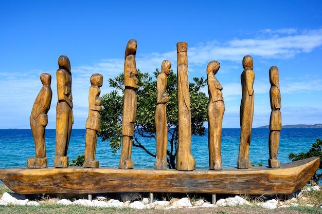 Holzstatue von menschen auf einem boot durch das meer in nea roda, chalkidiki, griechenland Premium Fotos