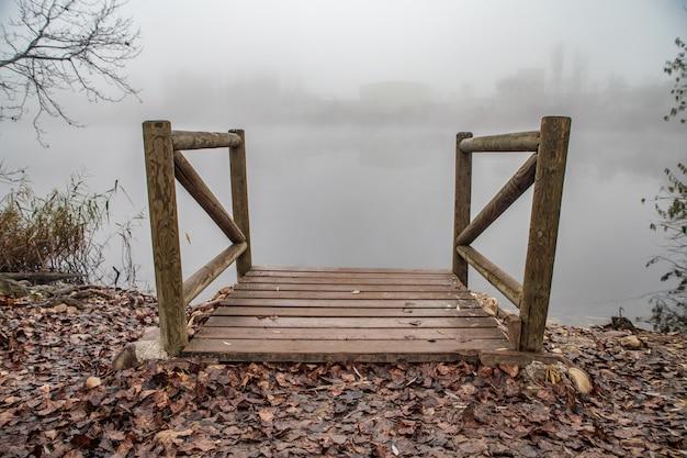 Holzsteg an einem see mit nebel Premium Fotos