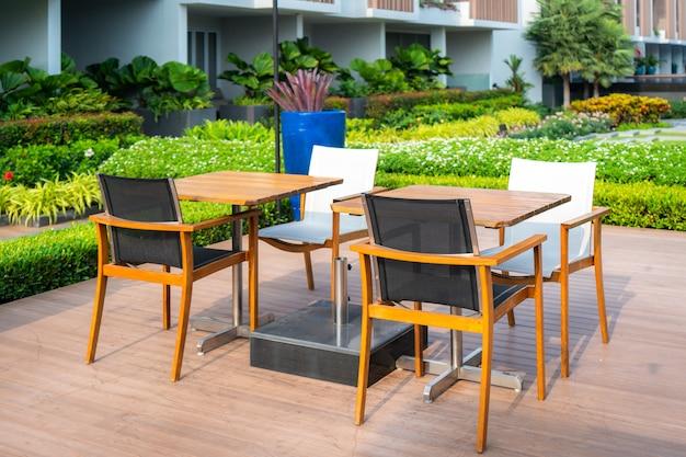 Holzstuhl im hölzernen patio am grünen garten im haus Premium Fotos