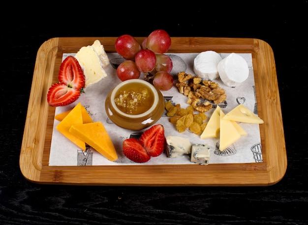 Holztablett mit käse, früchten und einem glas honig Kostenlose Fotos