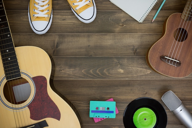 Holztisch des musikkomponisten, gitarre, ukulele, notizbuch, audiokassetten, mikrofon, tonbandgerät Premium Fotos