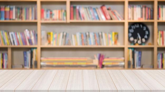 Holztisch in der bibliothek mit einem unscharfen bücherregal mit vielen buchen Premium Fotos