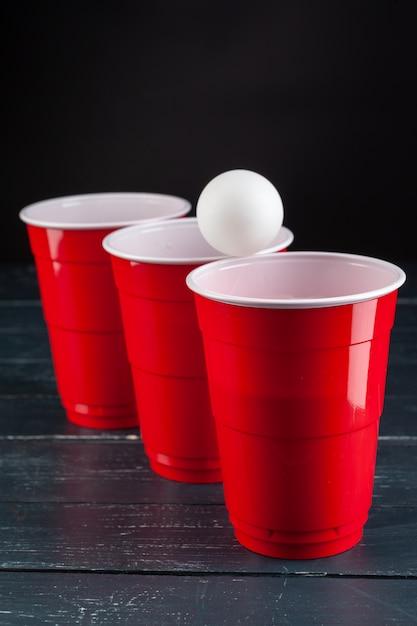 Holztisch mit roten schalen und ball für bier pong Premium Fotos
