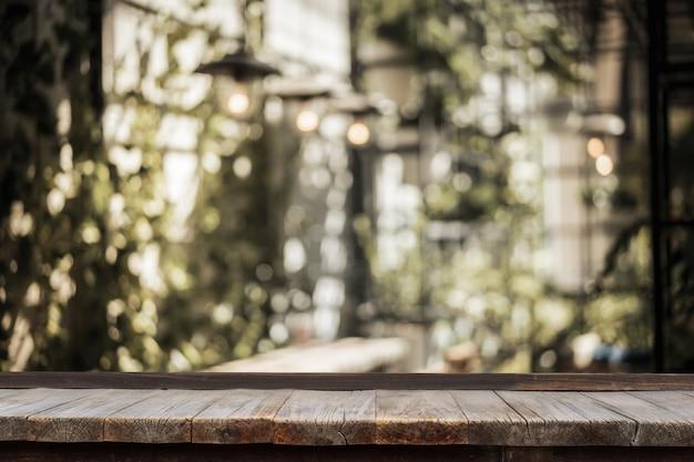 Holztisch vor innengarten mit der tabelle und glühlampe verziert Premium Fotos