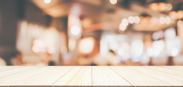 Holztischplatte mit restaurantcafé oder kaffeehausinnenraum mit abstraktem unscharfem unschärfehintergrund der leute Premium Fotos