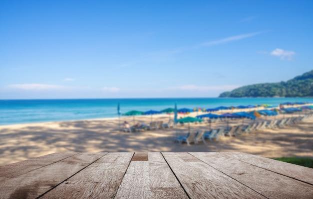 Holztischspitze auf unscharfem sonnenschirm und einige leute entspannen sich auf dem weißen sandstrand und dem blauen meer mit blauem himmel Premium Fotos