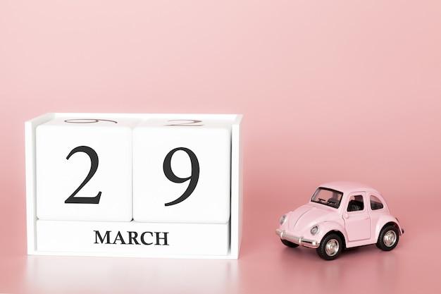 Holzwürfel 29. märz. tag 29 des märzmonats, kalender auf einem rosa hintergrund mit retro- auto. Premium Fotos