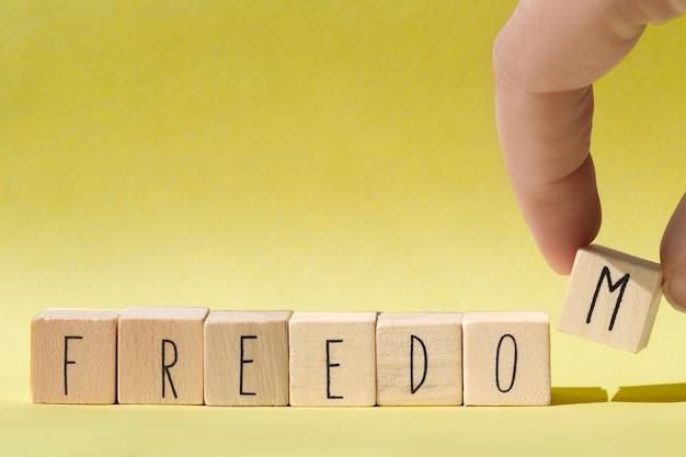 Holzwürfel mit dem wort freiheit, freiheit konzept hintergrund nahaufnahme Premium Fotos