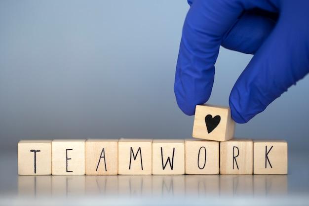 Holzwürfel mit den worten teamarbeit für geschäftskonzept oder krankenschwestern im gesundheitswesen oder arzt covid-19, coronavirus, arbeiten in teams weltweit Premium Fotos