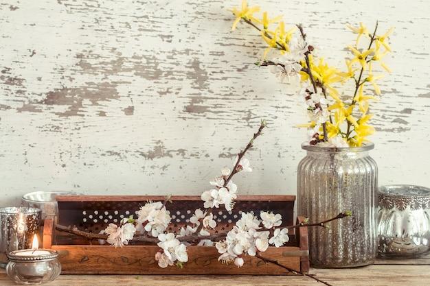 Home gemütliche schöne einrichtung, verschiedene vasen und kerzen mit frühlingsblumen, auf einem hölzernen hintergrund, das konzept der innendetails Premium Fotos