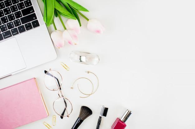 Home-office-arbeitsbereich. frauenmode. strauß rosen, notebook, make-up pinsel und zubehör auf einem weißen hintergrund. flache lage, draufsichtkopienraum. Premium Fotos