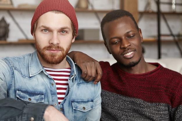 Homosexualität, interraciale beziehungen, liebes- und glückskonzept. männliche samesex-partner verbringen eine schöne zeit zusammen im café, sitzen nahe beieinander und sprechen über ihre zukunft Kostenlose Fotos