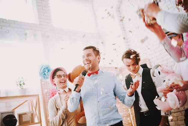Homosexuelle feiern zu hause eine party und singen ins mikrofon Premium Fotos