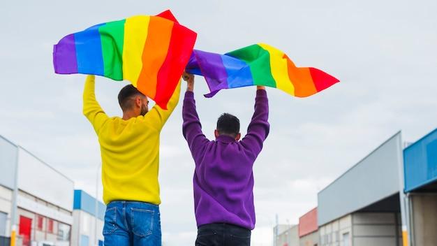 Homosexuelle halten wellenartig bewegende regenbogenflaggen Premium Fotos