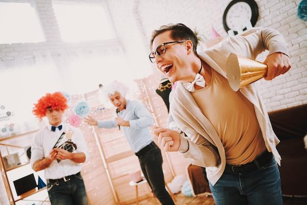Homosexuelle kerle in den fliegen, die zu hause an der partei tanzen Premium Fotos
